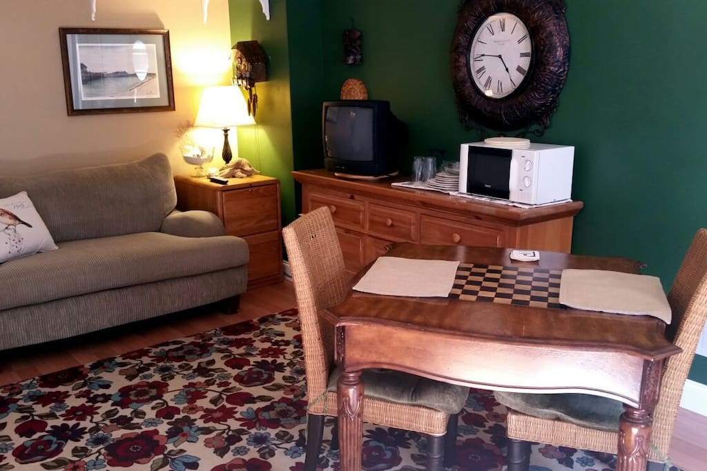 Sitting area with tv,  table and chairs.