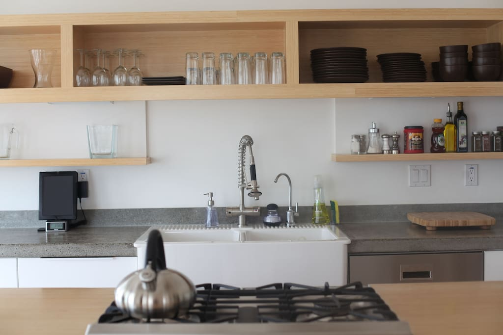 Modern kitchen with cooking items, coffee maker and grinder, ice maker, etc.