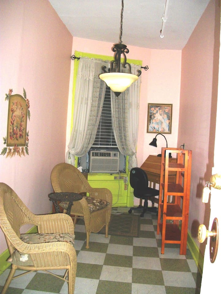 Desk, A/C, two easy chairs, shelving unit, small chest with drawers, closet.