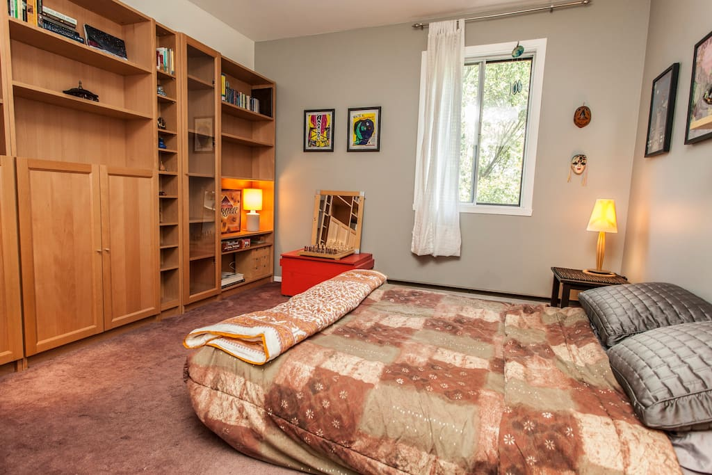 Relax in the guest bedroom amid an extensive library of books, decorated with posters from local Montreal artists.