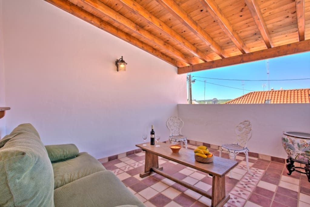 First floor covered terrace with sofa and coffee table