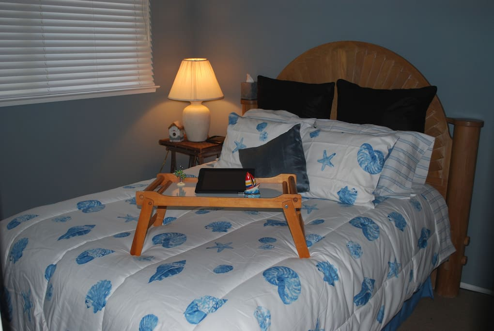 This is the second bedroom with a queen bed and a seashell motif.