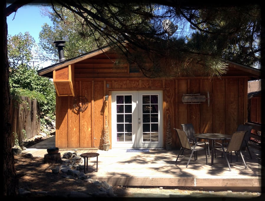 The Hideaway's deck with seating for four underneath towering pine trees. Not shown: gas BBQ grill around the corner.
