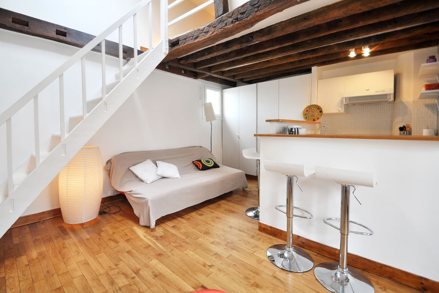 The stairs bring you to the cosy sleeping area in the attic. The sofa is a bed as well. The bar and the open kitchen