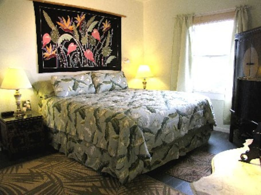 Master Bedroom w/ KingSize Bed, Armoire and private Lanai facing the back of the house w/ gardens and ponds.