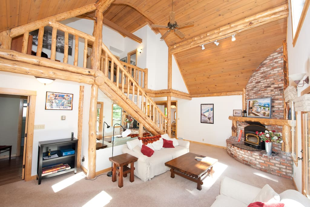 Living Room with huge brick fireplace, wood burning stove and natural log peeler accents abound