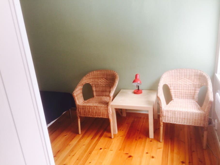 Two Chairs and a table placed by the window