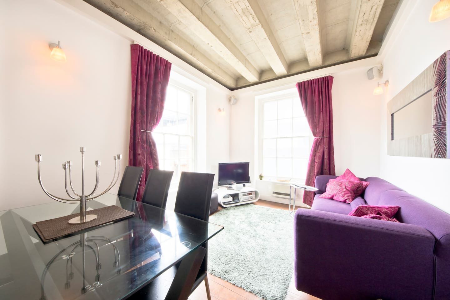 Designer lounge with full dining table and dual aspect windows, overlooking a quiet courtyard in the heart of Soho, London.