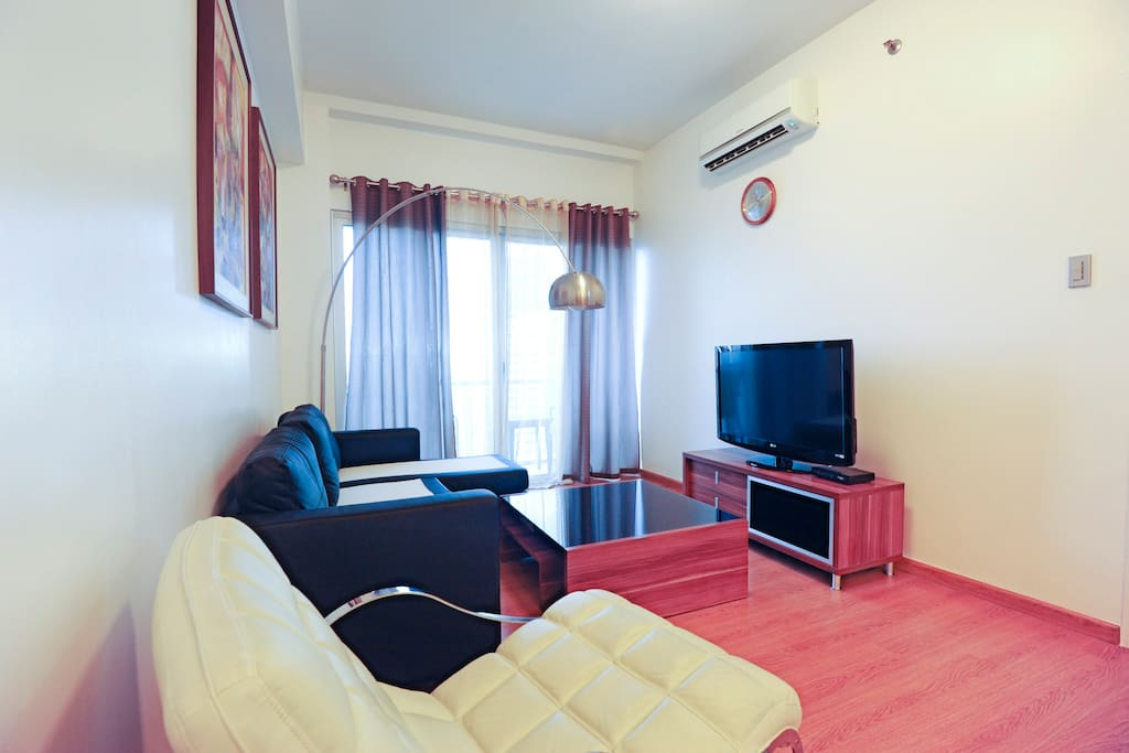 air conditioned living room area with balcony.