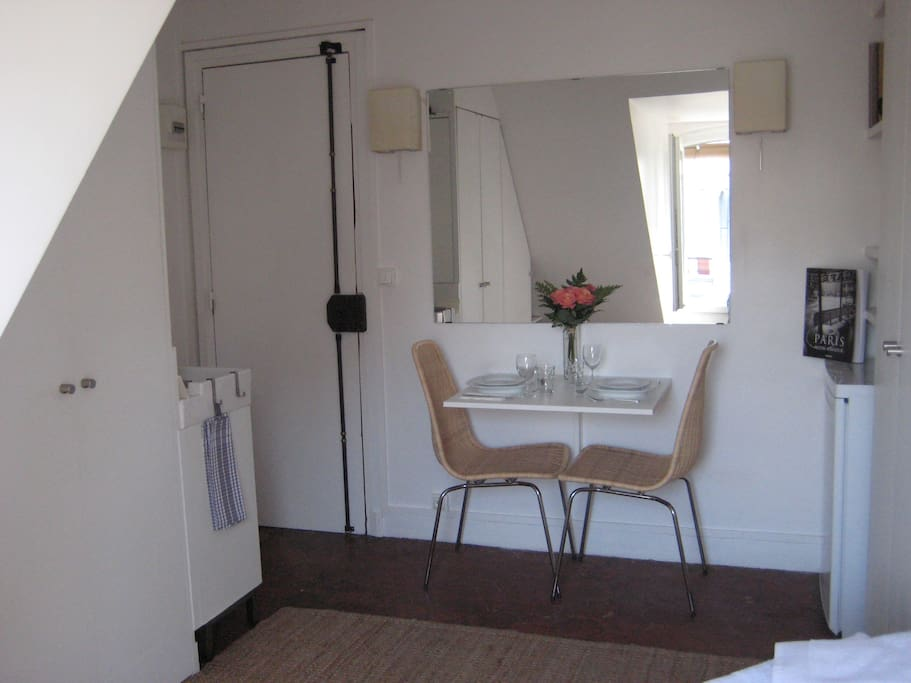 Perspective of the studio entrance with the toilet, table an kichenette area