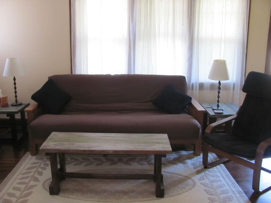 Living room with another full size futon, cable TV, and ceiling fan