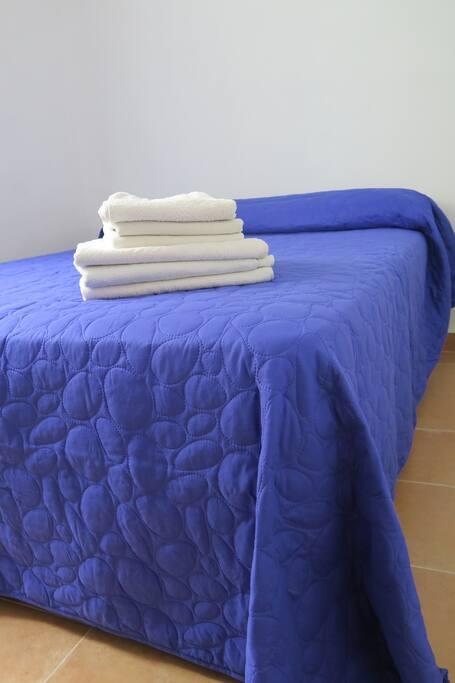 La cama de matrimonio en una habitación luminosa y amplia