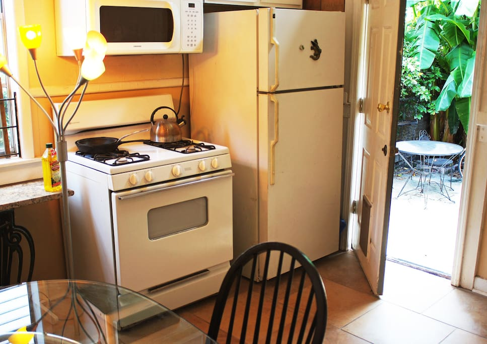Kitchen and rear patio. Gas stove/oven, new microwave. Washer/dryer in utility shed by patio.