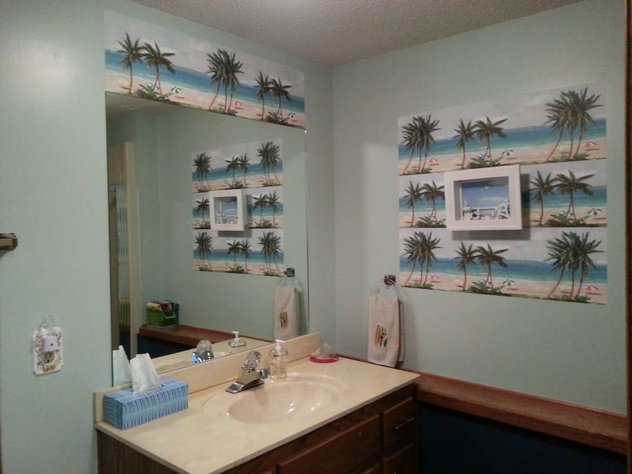 Beach-themed private bathroom with shower stall.