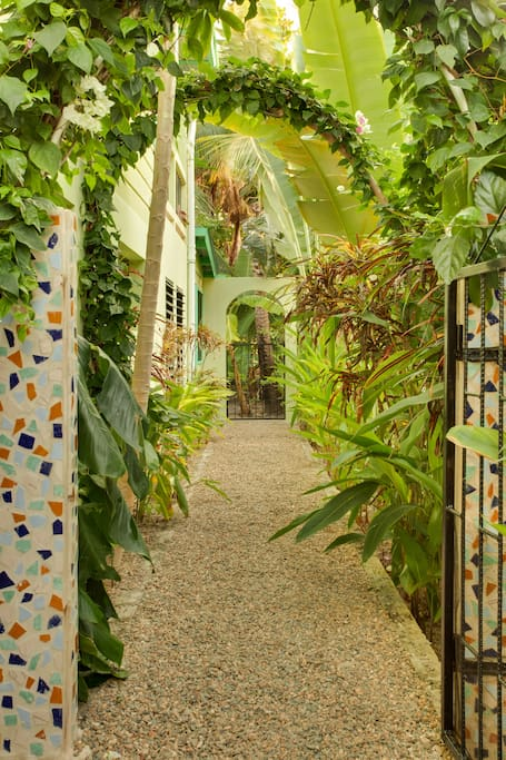 Enter private gate surrounded by mosaic tiled columns & lush tropical flowers.....