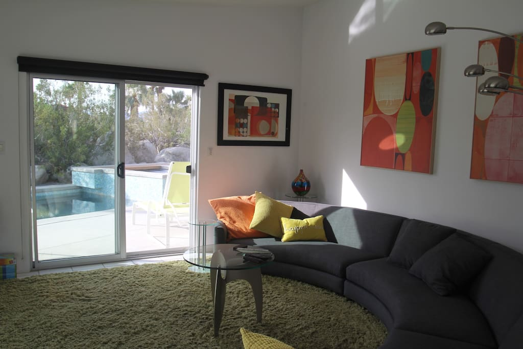 Circular couch in living space, overlooks the pool and 1400 sq ft patio
