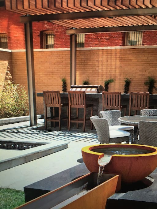 Courtyard bar set up with bbq , bocce, fountain, lots of comfortable seating