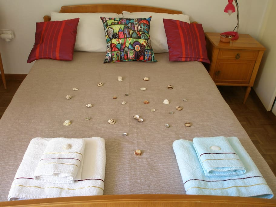 the bedroom with the double bed and clean colourful towels