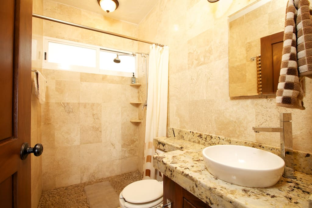 Upstairs full marble bath with pebble bottom shower