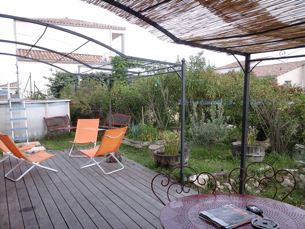 Terrasse sud avec coin repas ombragé piscine et bains de soleil