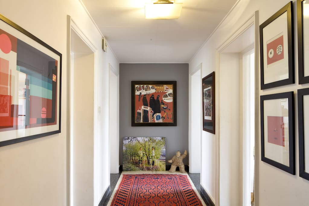 hallway with antique rug and art from ethiopia, vietnam and china.