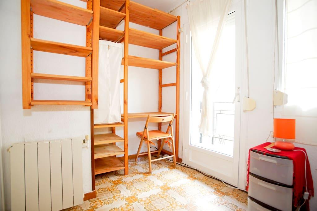 La habitación tiene un escritorio,varias estanterias y un armario pequeño