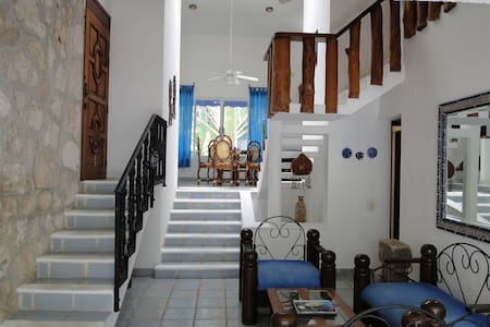 Spacious 2 bed family friendly house 100m from the beach. There are 2 large living rooms, kitchen and dining area plus front and back patios. The house is just a 5 block/8 min walk to the main town square and the many restaurants, bars & shops.