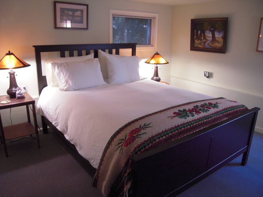 Bedroom. Comfy queen-size bed with good linens and four pillows of varying heft and density. Five-drawer dresser, mini-closet,  windows on two sides, lamps with mica shades. Very well-insulated.