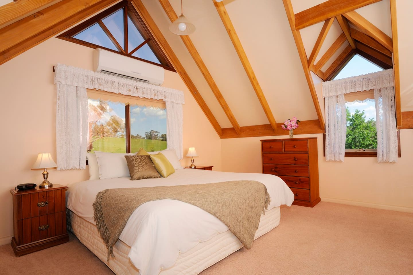 Upstairs in the loft cottages you will find a large air conditioned bedroom with soaring cathedral ceilings, a king size bed, and stunning views across the property