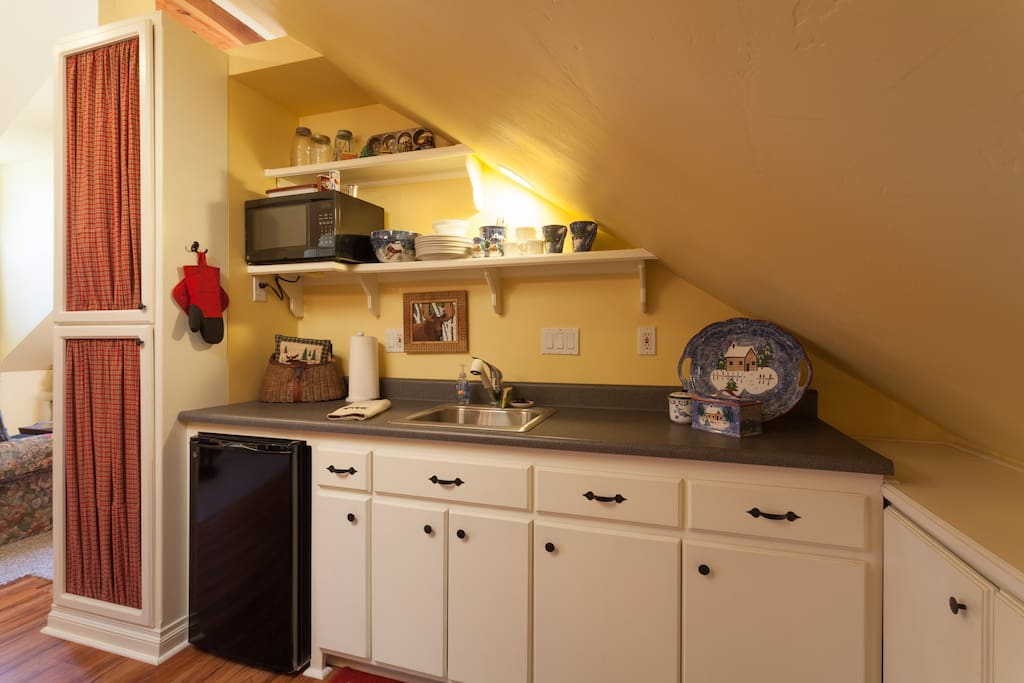 Serving and eating dishes, glassware and utensils are stored out of sight in the kitchenette's pantry.