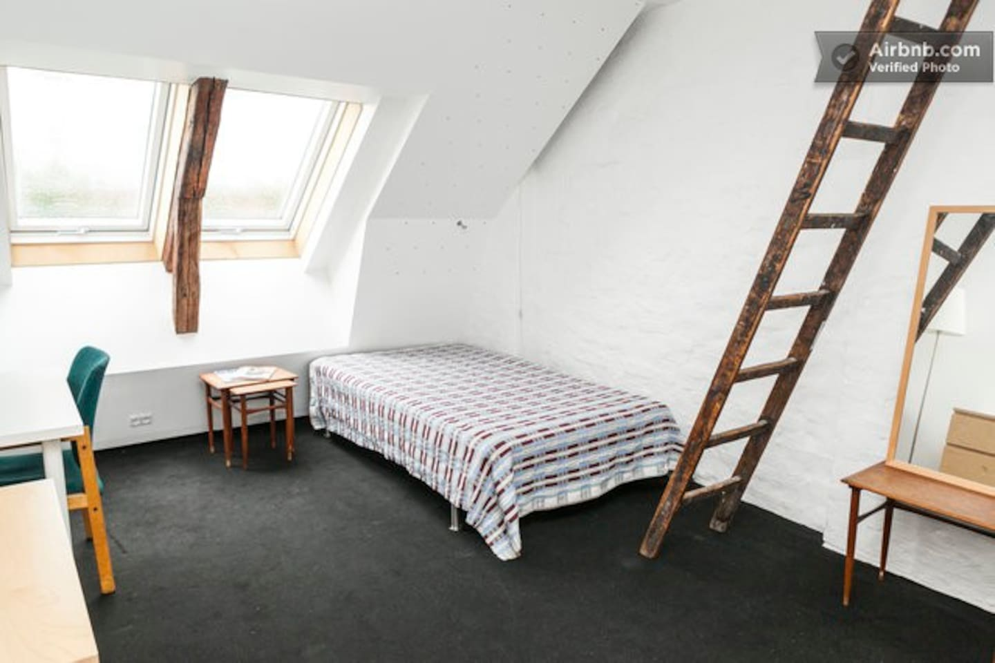 Main room with comfortable double bed and desk.
