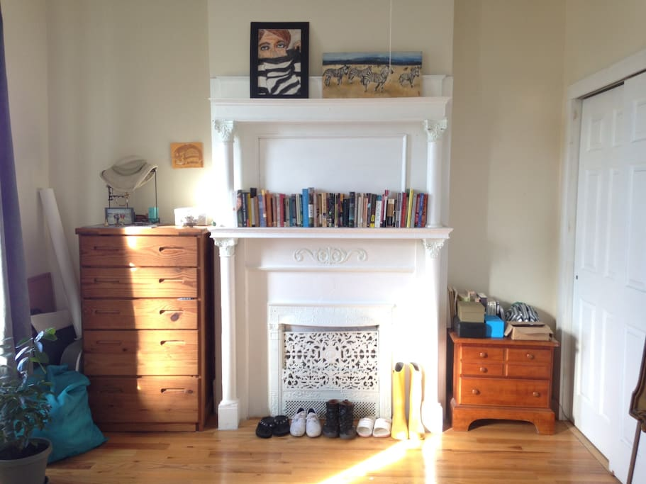 The bedroom includes a full sized bed, ornamental fireplace, dresser, and lots of closet space