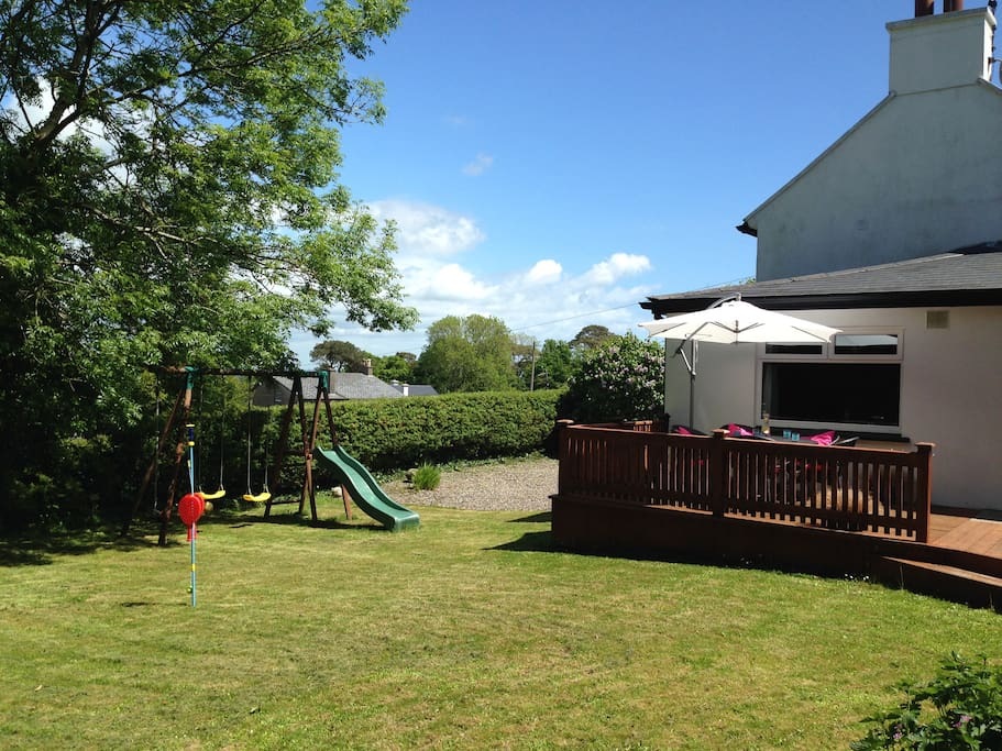 Semi-enclosed garden with children's swings / slide set and sundeck area.