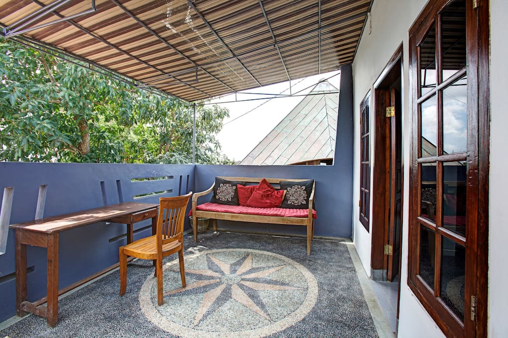 outdoor, covered sitting area with huge mango tree