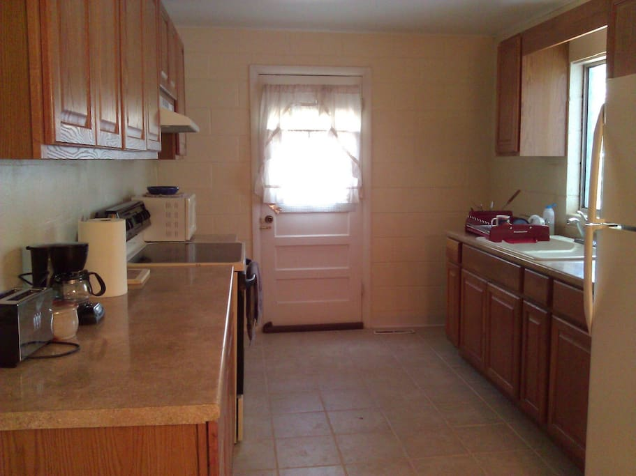 Full kitchen with dishes, pots, pans, coffee maker, toaster, fridge, microwave, electric stove