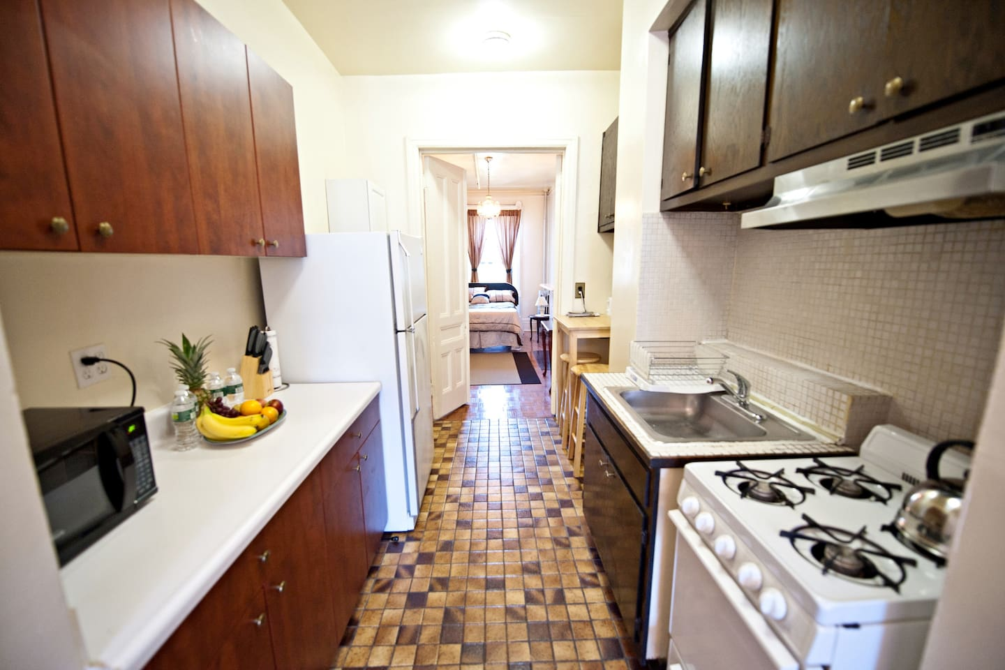 A spacious kitchen with water and fruits to welcome the guests