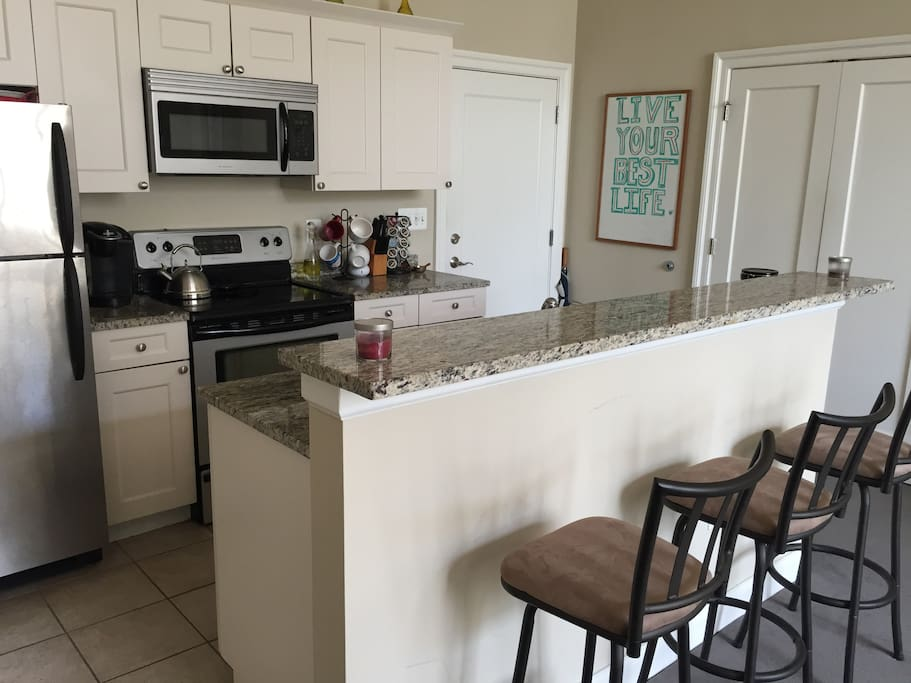 Breakfast Bar and Kitchen with Granite Top Counters, Full Oven, Microwave, Dishwasher, Refrigerator, Dishes, Glasses, Silverware, Cookware, Garbage Disposal, Keurig Coffeemaker.