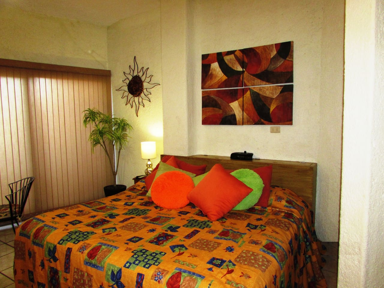 Cozy king size bed and alarm clock, vibrant decoration. Room has vertical blinds that twist to let the morning sunshine in or twist the other way for privacy.