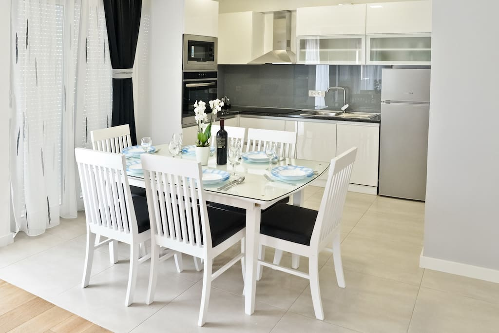 large kitchen with various appliances ( microwave , coffee maker , fridge , electric kettle , dishwasher)