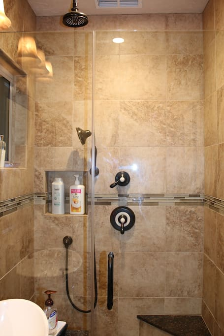 The new shower has both rainfall and hand-held shower heads in oil-rubbed bronze.  There are toiletries for you to use and a small built in bench.