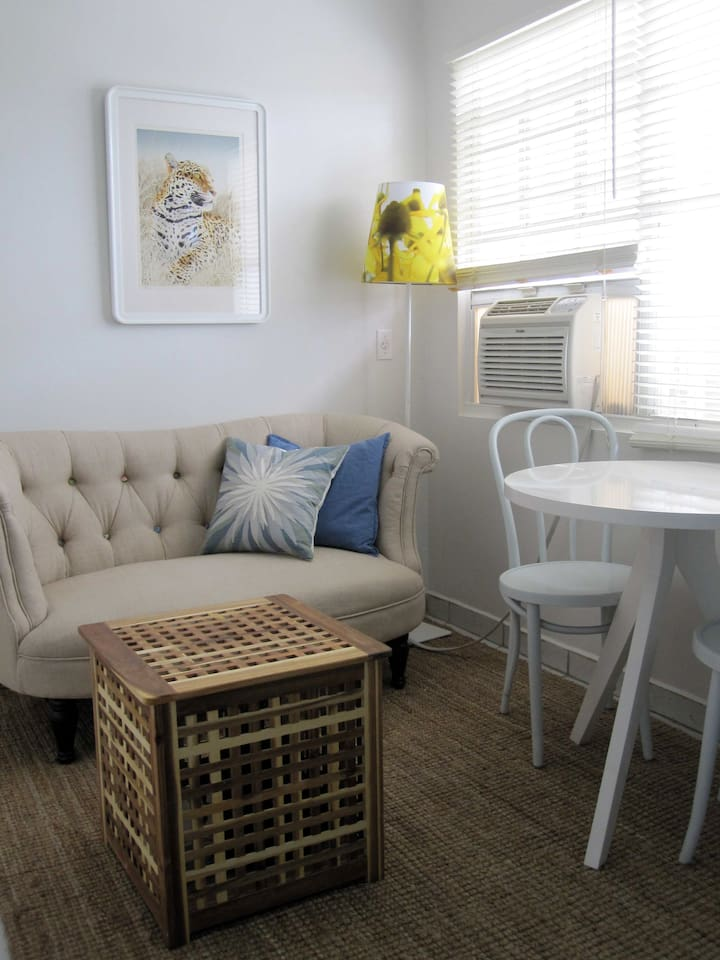 Living area with couch, dining, coffee table with storage and wall mount AC unit
