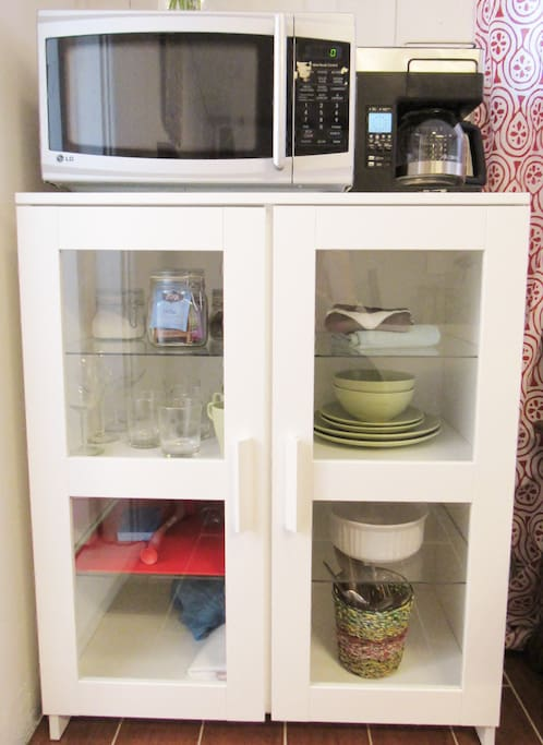 The comforts of home: microwave, coffee pot, coffee/tea, glassware, dishes, and flatware