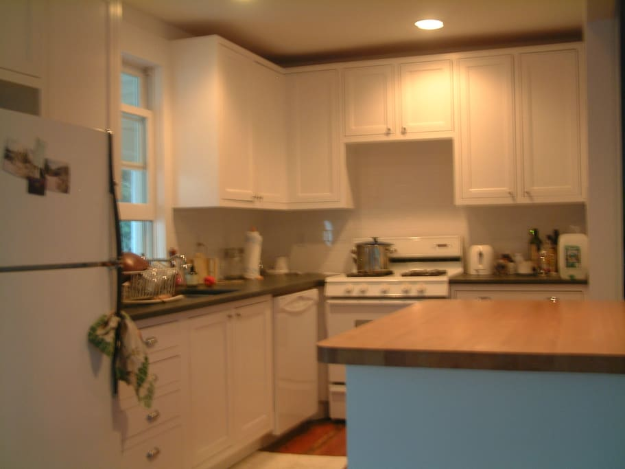 Kitchen with dishwasher, gas stove, fridge, microwave, stone and wood countertops