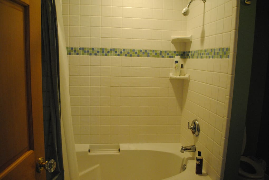 private tiled bath with tub and shower