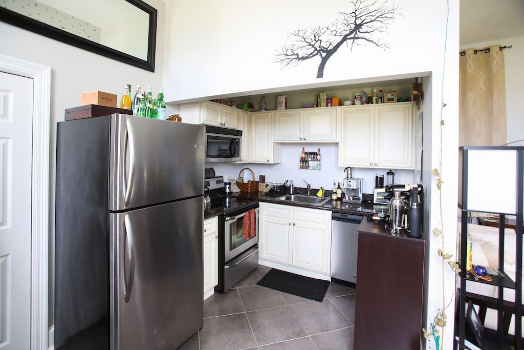 Full kitchen with stainless appliances, espresso machine.
