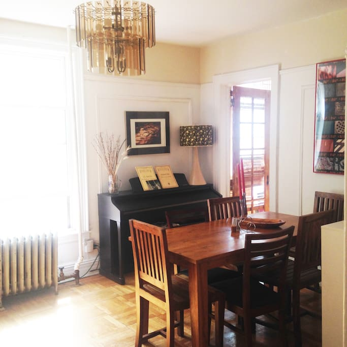 Dining room with piano. Door open to second bedroom.