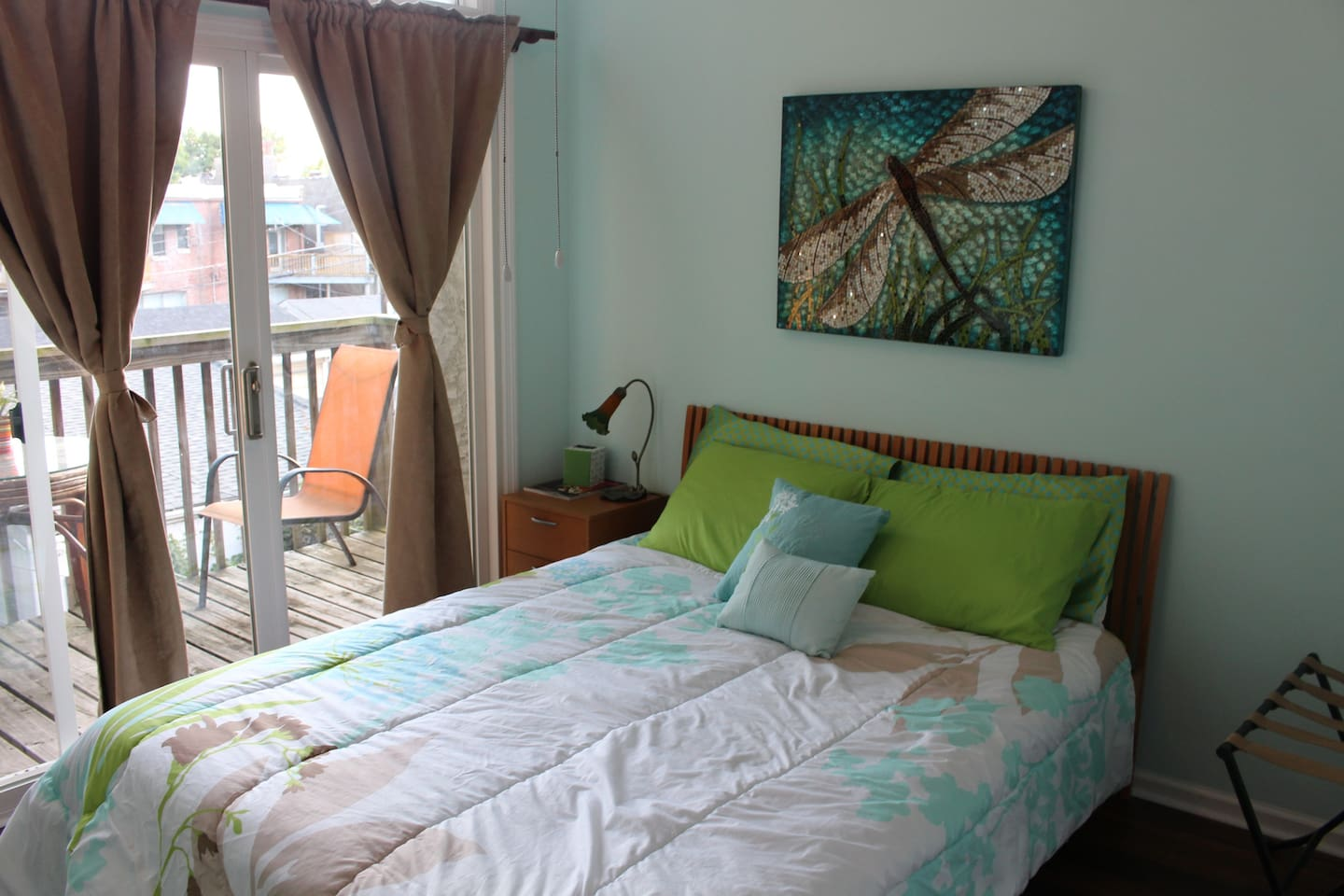 Comfortable queen size bed in a bright, sunny room.