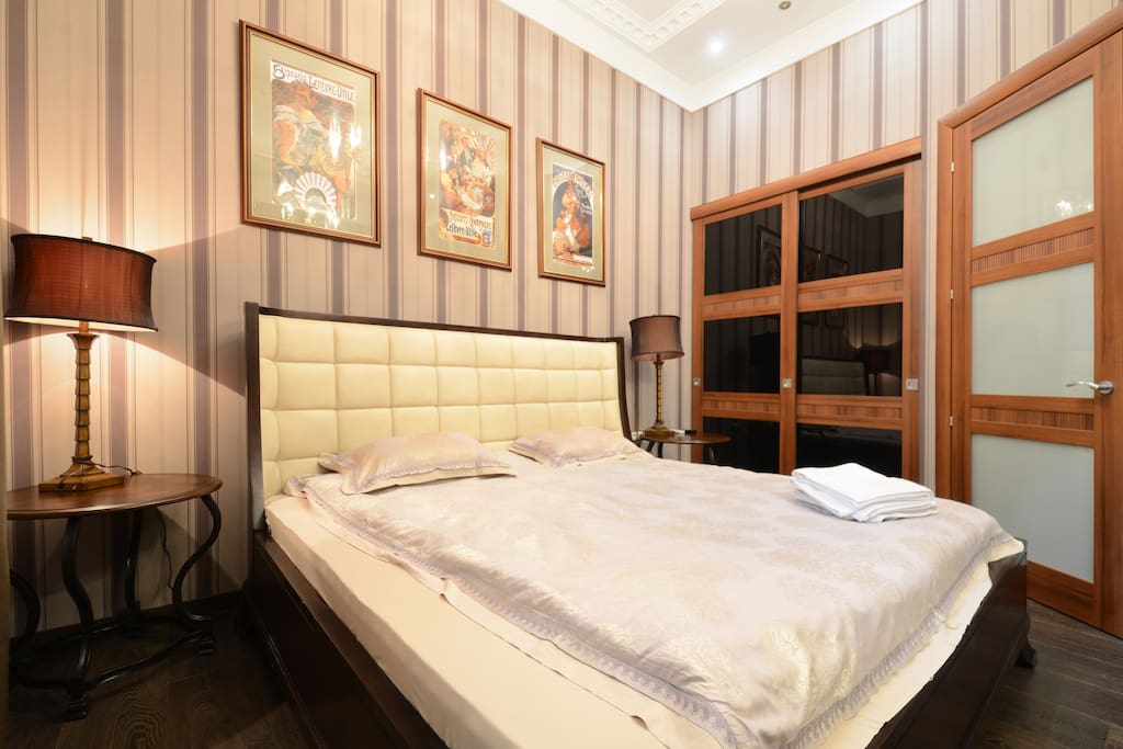Comfortable bedroom with real american Queen-size bed, 2 night tables, airconditioner, flat screen TV, wardrobe and big mirror on the wall.