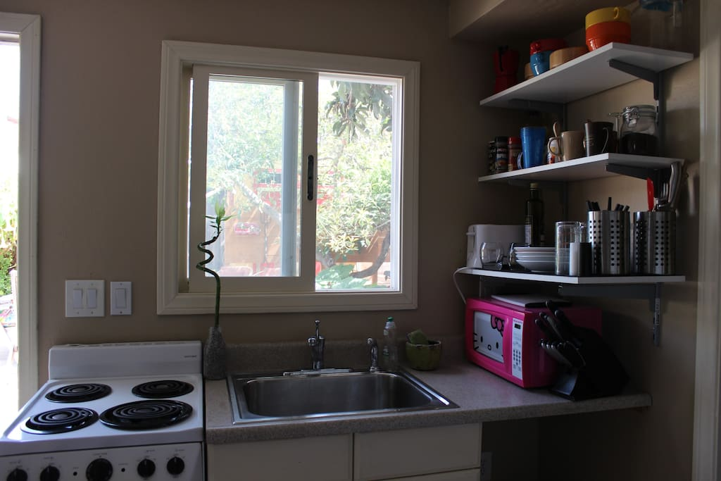 small, but full-functioning kitchen. Equipped with an oven, stove top, microwave, toaster, and sink.