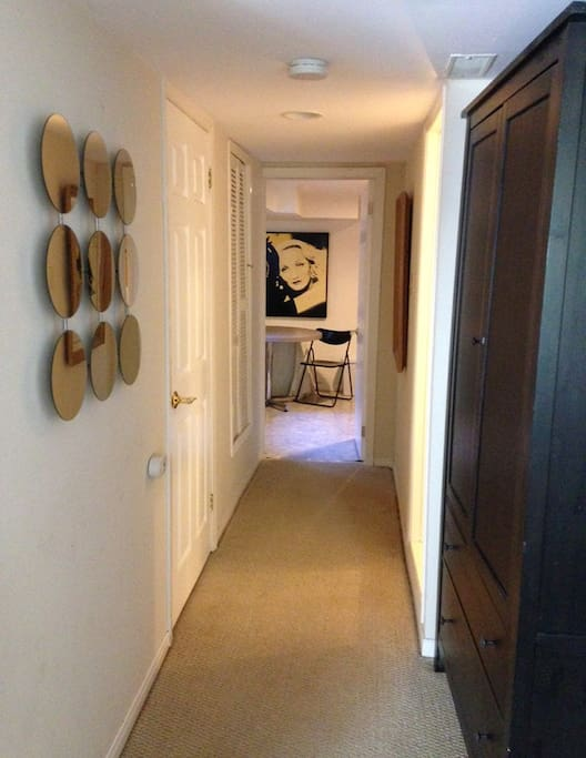 The hallway view to the kitchen. On the right is a tall wardrobe with hangers and two deep drawers.